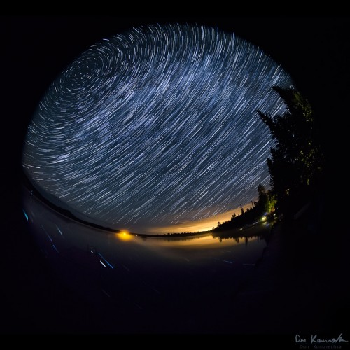 circular fisheye star trail image over a lake