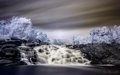 Infrared photo of a false-colour waterfall landscape